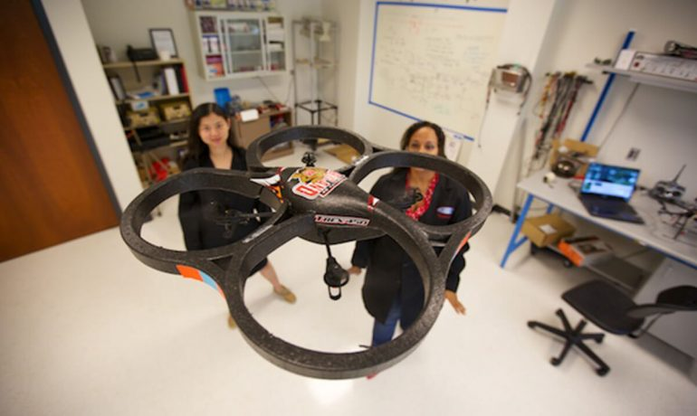 Female NIA researchers flying drone in lab