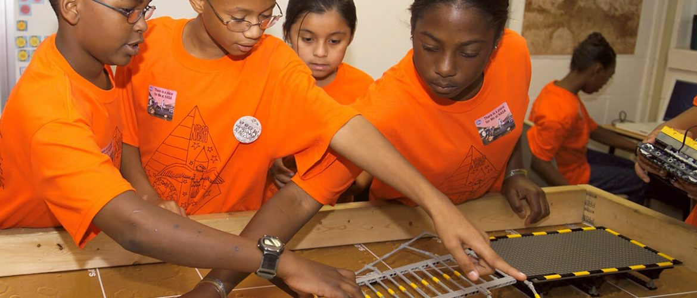 Kids exploring space technology through lego kit models