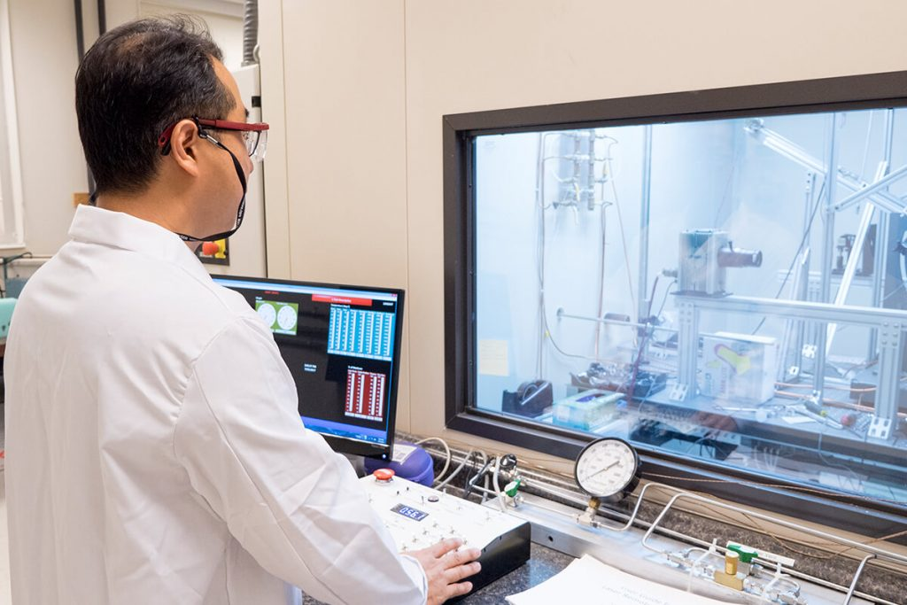 Scientist monitors test of machinery from window