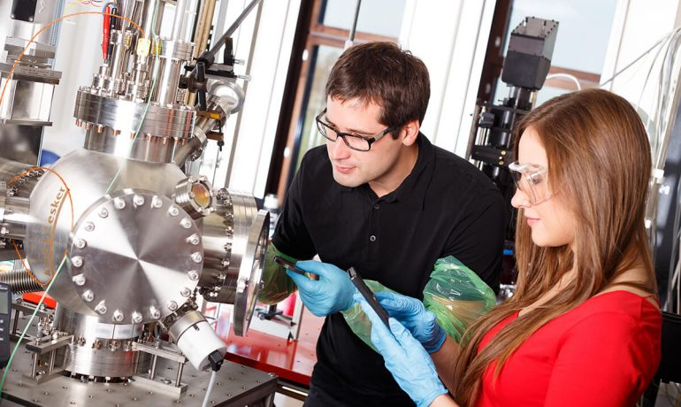 Research scientists working with laser deposits chamber technology