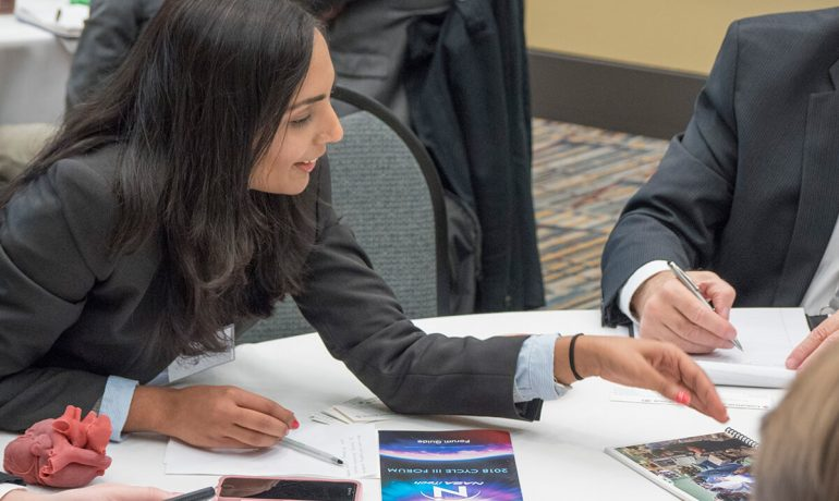 Woman discussing with small group at table during 2018 NASA iTech forum event
