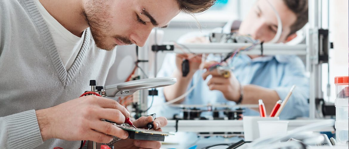 Two male engineers working in a lab with voltage and current tester and a 3D printer