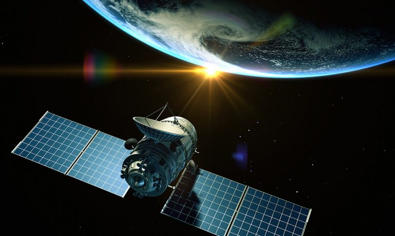 Satellite floating in space with Earth in view and the sun starting to rise